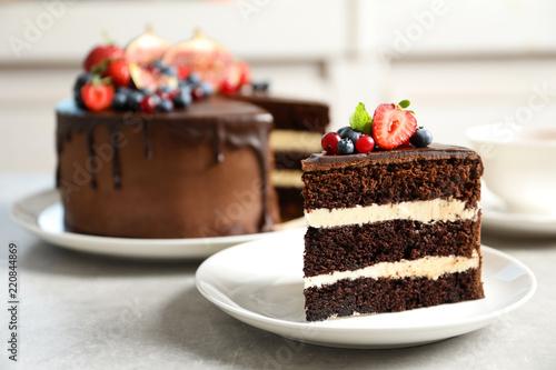 Valokuvatapetti Plate with slice of chocolate sponge berry cake on grey table