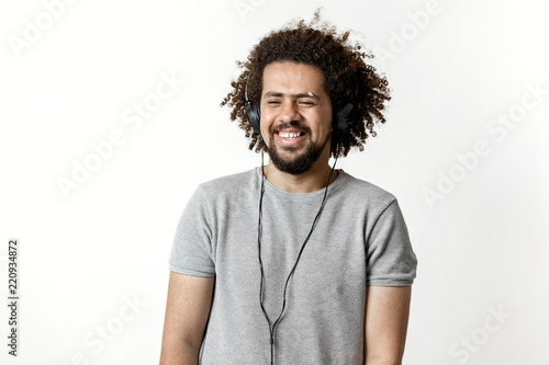 Fotografija A curly-headed handsome man wearing a gray T-shirt and ripped jeans is standing and listening to music in the headphones and laughing over the white background