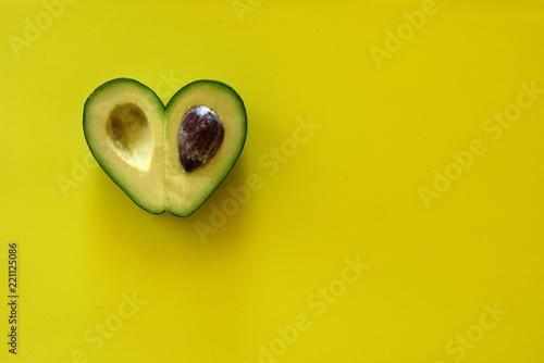 Heart-shaped avocado on yellow background