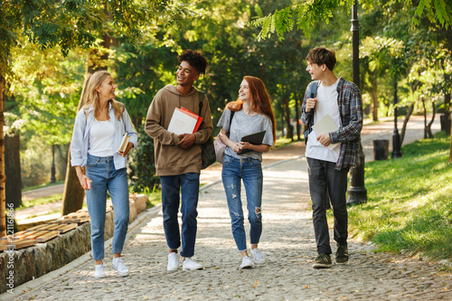 Group of happy students walking at the campus