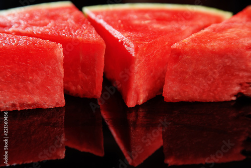 Sliced ripe red watermelon close-up on a black background