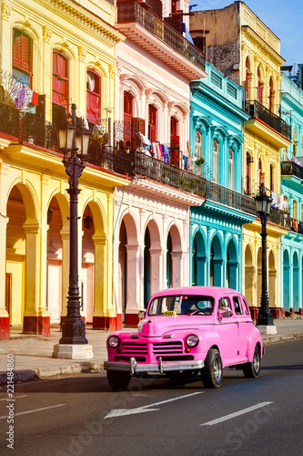 Classic car and colorful buildings at sunset in Old Havana