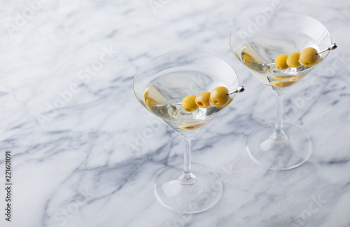 Martini cocktail with green olives on marble table background. Copy space.