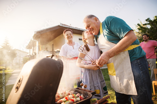 Proud grandparents are having great time with their granddaughter, while making barbeque in backyard.