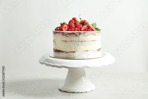 Delicious homemade cake with fresh berries on stand against light background