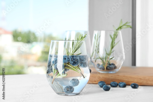 Refreshing blueberry cocktail with rosemary on table
