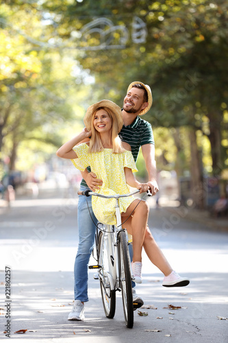 Happy couple riding bicycle together on street