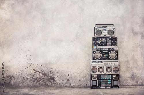 Fototapeta premium Retro old school design getto blaster boombox stereo radio magnetofon kasetowy wieża z przodu z betonowej ściany z lat 80-tych. Filtrowane zdjęcie w stylu vintage
