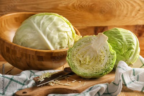 Fototapeta Whole and cut fresh cabbage on wooden table