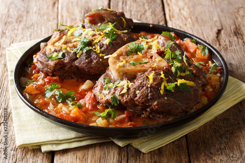Italian menu: braised veal steak Ossobuco alla Milanese with gremolata and vegetable sauce close-up. horizontal