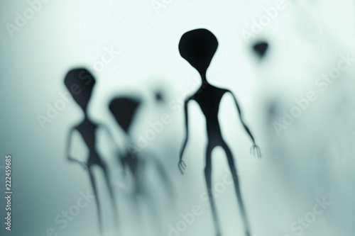 Foto Spooky silhouettes of aliens and bright light in background