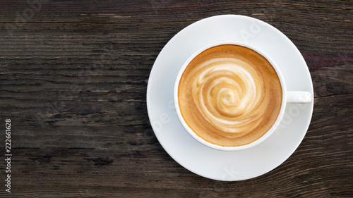 Photographie Hot coffee cappuccino latte spiral foam top view on dark wooden background