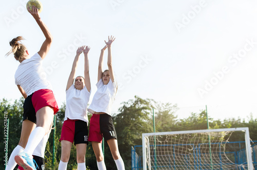 Handball players in defence of a goal