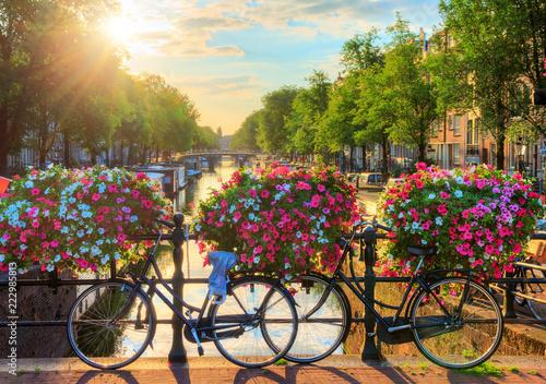 Fototapeta premium Piękny letni wschód słońca nad słynnymi kanałami światowego dziedzictwa UNESCO w Amsterdamie w Holandii, z żywymi kwiatami i rowerami na moście