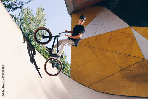 BMX rider makes a TAilwhip trick. Young man doing tricks in the air on a BMX bike. BMX freestyle