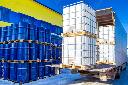 Discharge of plastic barrels. Barrels for the chemical industry. Blue metal barrels. White plastic containers. Chemical industry. The machine brought chemical substances.
