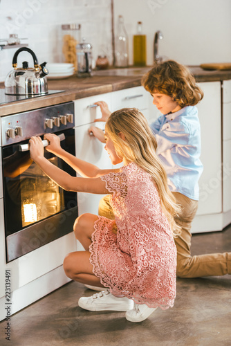 Fotografie, Tablou adorable kids looking at baking oven at kitchen