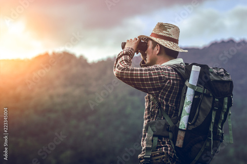 Tablou Canvas hiker with backpack standing looking through binoculars on the mountain