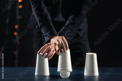 Obraz na płótnie Magician showing tricks with cups on dark background