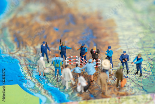 Valokuvatapetti Miniature toy people concept US border patrols against a group of migrant from M