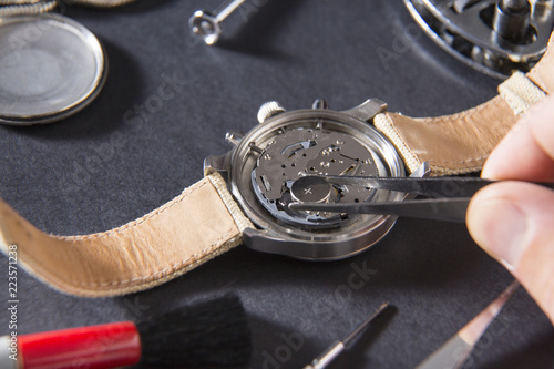 Detail of the work of a watchmaker who replaces a battery / Close up of replacing a watch battery with watchmaker tools
