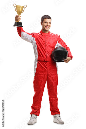 Racer standing and holding a helmet and a gold trophy cup