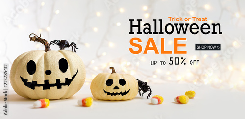 Halloween sale message with pumpkins with spider on a shiny light background