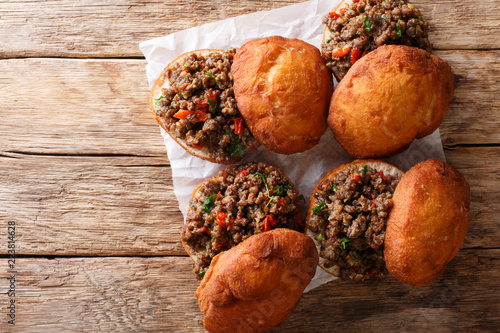 Delicious South African Vetkoek fried donuts stuffed with minced meat close-up. horizontal top view