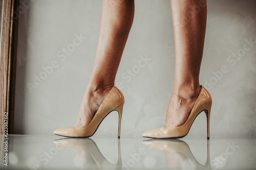 Obraz na plátně Close up fashion feet wearing contemporary beige shoes on high heels indoor
