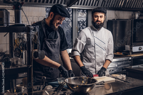 Two smiling bearded cooks dressed in uniforms preparing sushi in the kitchen Fototapet