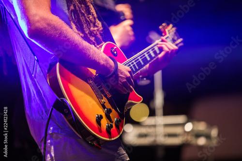 Obraz na plátně Guitarist playing on electric bass guitar on stage