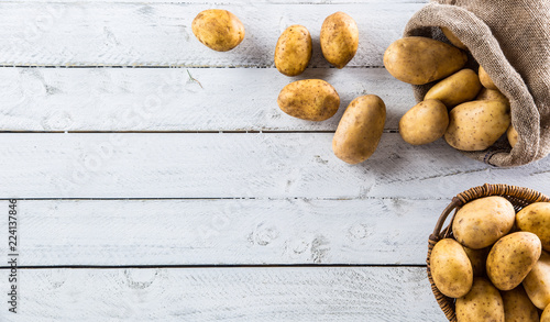 Ripe potatoes in burlap sack freely lying on board.