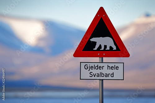 """Red road traffic sign with Polar bear. """"Gjelder Hele Svalbard"""" means """"Over All of Svalbard (watch out for polar bears)"""". Polar bear with snowy mountain, Svalbard. Travelling in the Arctic."""