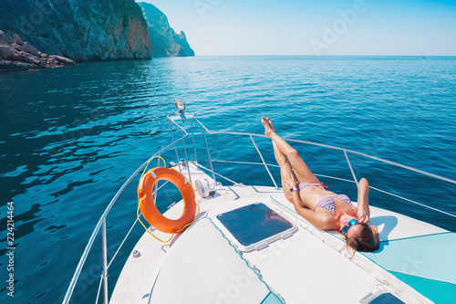 Woman on a Yacht in the Sea. Luxury vacation on a boat near the islands in the summer. Beautiful sexy girl relaxing and sunbathing on the deck. Cruise.