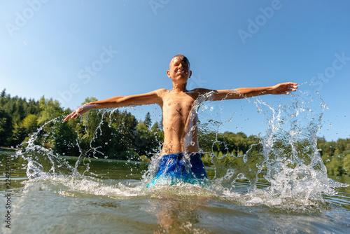Boy emerging from under water with big splash in wood lake Fototapeta