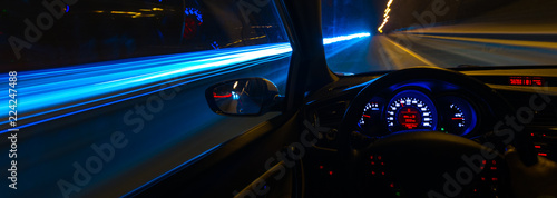 Stampa su Tela Movement of the car at night at a speed view from the interior, Brilliant road w