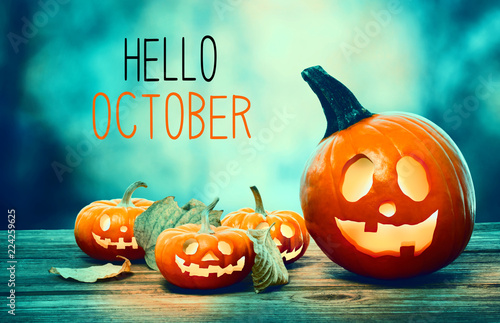 Hello October with pumpkins on a spooky forest at night