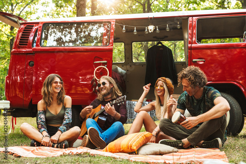 Платно Group of friends hippies men and women laughing, and playing guitar near vintage