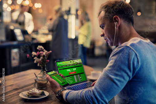 Man using online sports betting services on phone and laptop Fotobehang