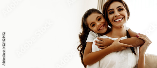 Family. Love. Togetherness. Portrait of happy mom and daughter hugging, looking at camera and smiling; at home