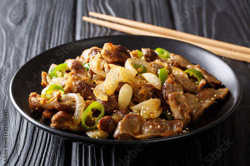 South Korean fried chicken gizzard with jalapeno pepper, onion, garlic and sesame close-up on a plate. horizontal