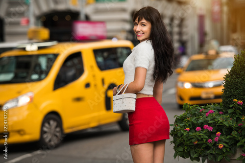 Photo Beautiful elegant smiling woman walking to yellow taxi on city street of New Yor