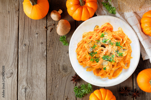 Pasta with a pumpkin, mushroom cream sauce. Autumn meal. Top view scene on a wood background with copy space.