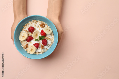 Woman holding bowl with oatmeal and fresh fruits on color background