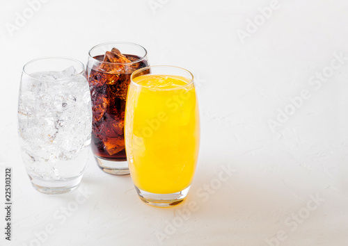 Glasses of soda drink with ice cubes and bubbles on stone kitchen table background. Cola and orange lemonade soda