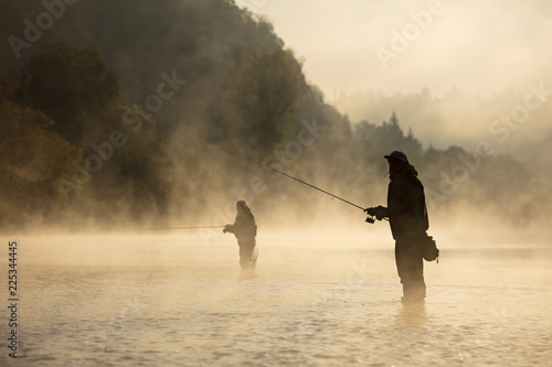 Men fishing in river with fly rod during summer morning.