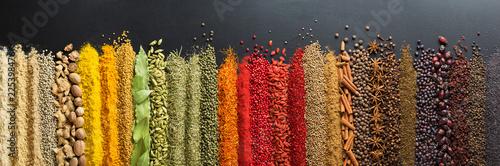 Fototapeta Kolorowe przyprawy, ułożone rzędami na ciemnym stole na płytki