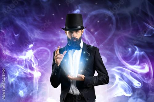 Photo Magician showing tricks in smoke on dark background
