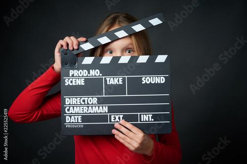 Fotografía Happy smiling girl holding clap board peeping, over dark background