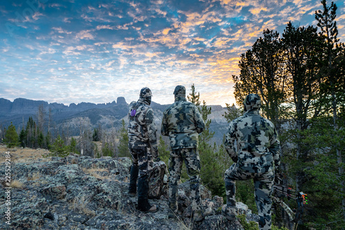 Obraz na plátne Three adult male hunter friends, unrecognizable,  stand on a mountain ridge looking for elk to hunt during bow archery season